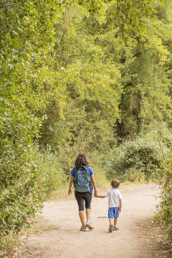 Una donna e un bambino che fanno trekking, camminando lungo una strada sterrata immagini stock