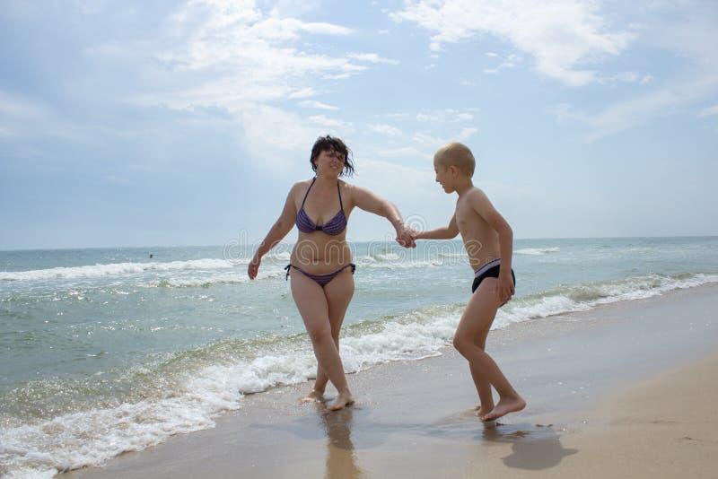 Una donna e un figlio che si tengono per mano in mare fotografie stock libere da diritti