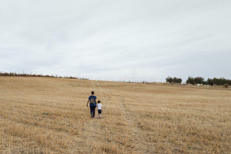 Una donna e un ragazzo che camminano attraverso un campo di grano falciato fotografia stock libera da diritti