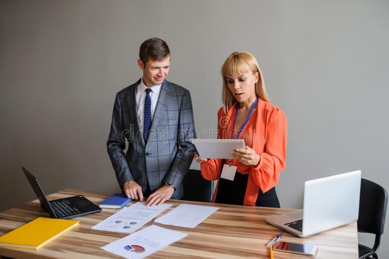 Una donna e un uomo di affari ad una scrivania che funziona al progetto fotografia stock libera da diritti