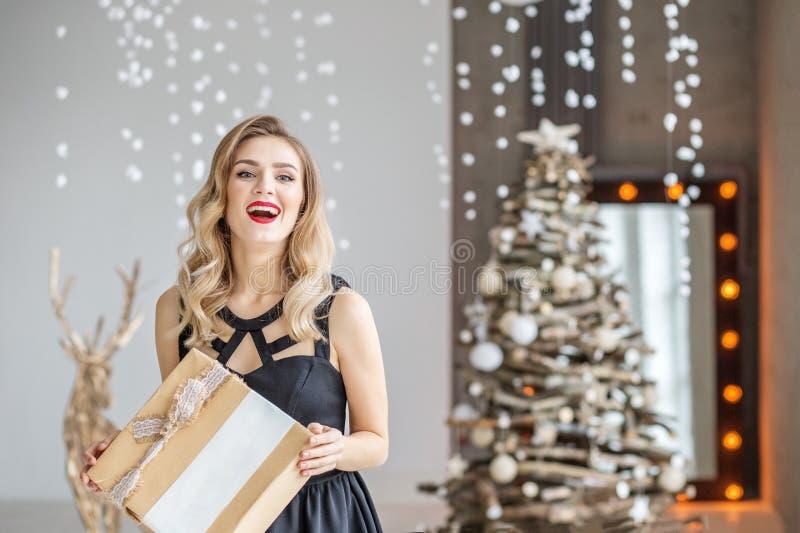 Una donna emozionale ha ottenuto un contenitore di regalo di sorpresa La ragazza in Dott. nero fotografia stock libera da diritti