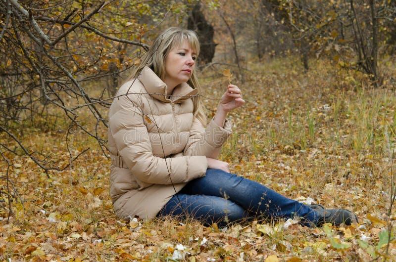 Una donna esamina la depressione in foglia di giallo di autunno immagini stock libere da diritti
