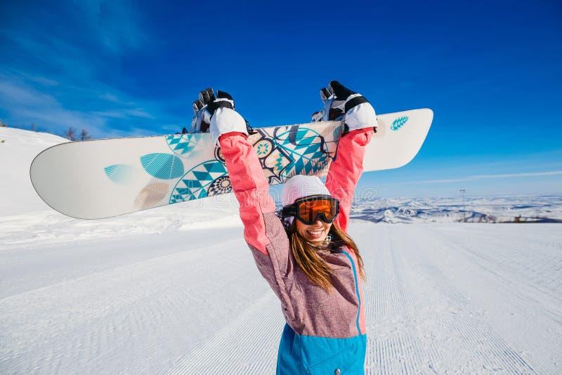 Una donna felice in vestito e vetri di sci tiene uno snowboard in sue mani immagine stock libera da diritti