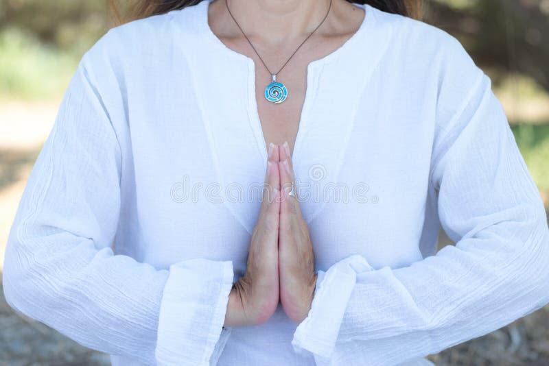 Una donna in gesto di nome si chiude, praticando yoga e meditazione all'aperto Indumenti bianchi di gioielleria boho chic fotografia stock libera da diritti