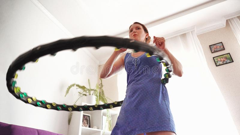 Una donna gira un hula-hoop a casa auto-addestramento con un cerchio fotografia stock libera da diritti
