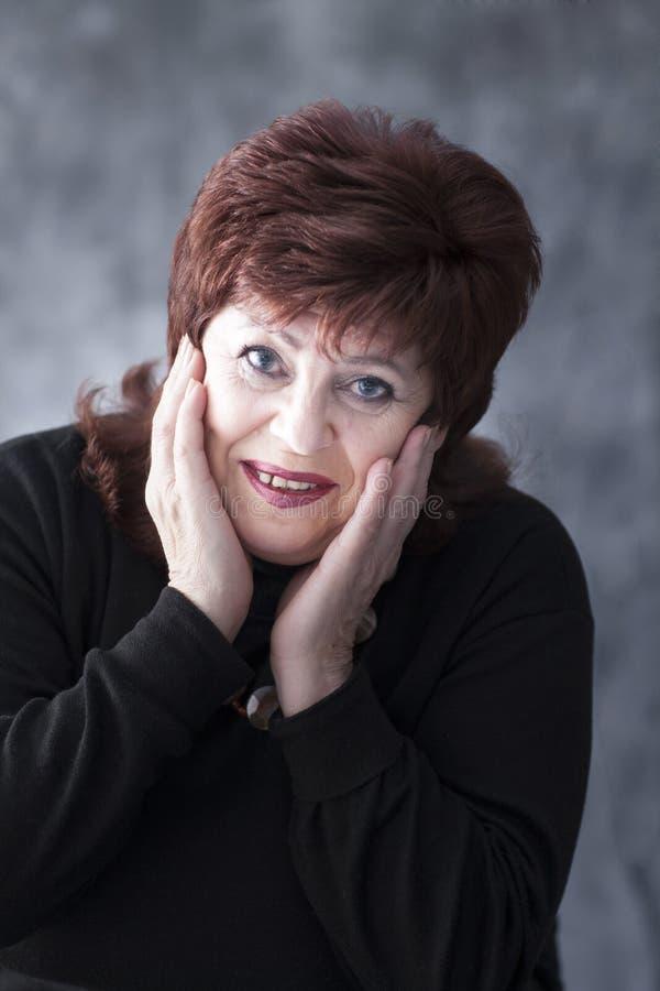 Una donna grassa in un maglione nero fotografie stock