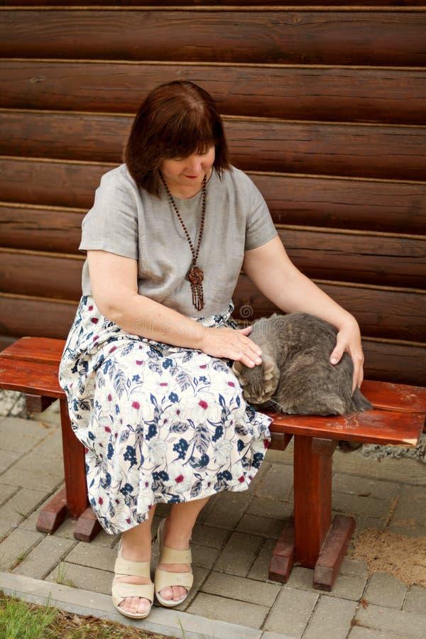 Una donna grassottella adulta si siede su un banco vicino ad una casa di ceppo e segna un gatto grigio immagine stock libera da diritti
