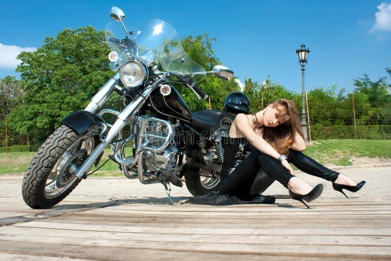 Una donna graziosa che colloca vicino in motocicletta immagini stock