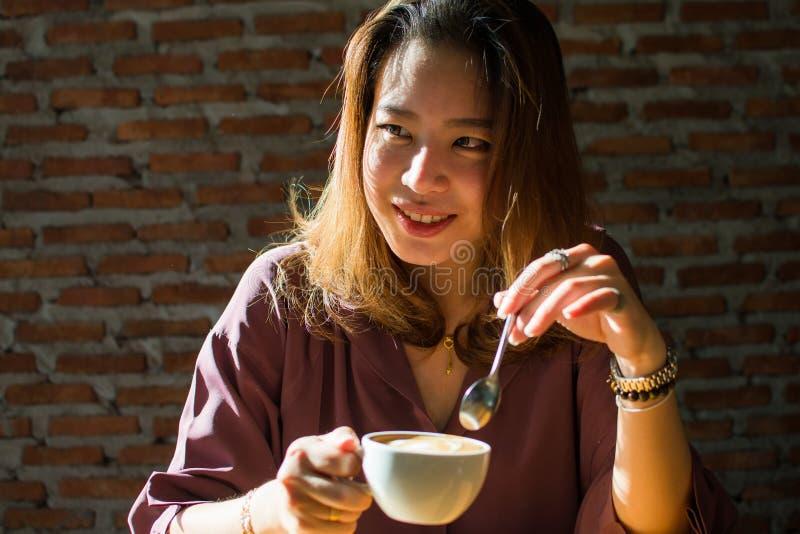 Una donna graziosa sta esaminando qualcuno mentre beveva il caffè fotografia stock libera da diritti
