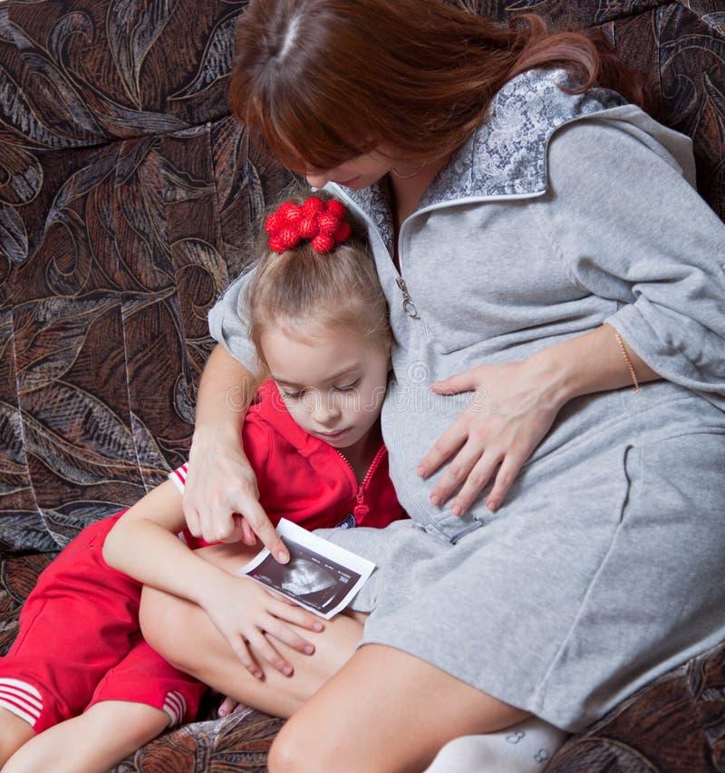 Una donna incinta con la sua figlia immagini stock libere da diritti