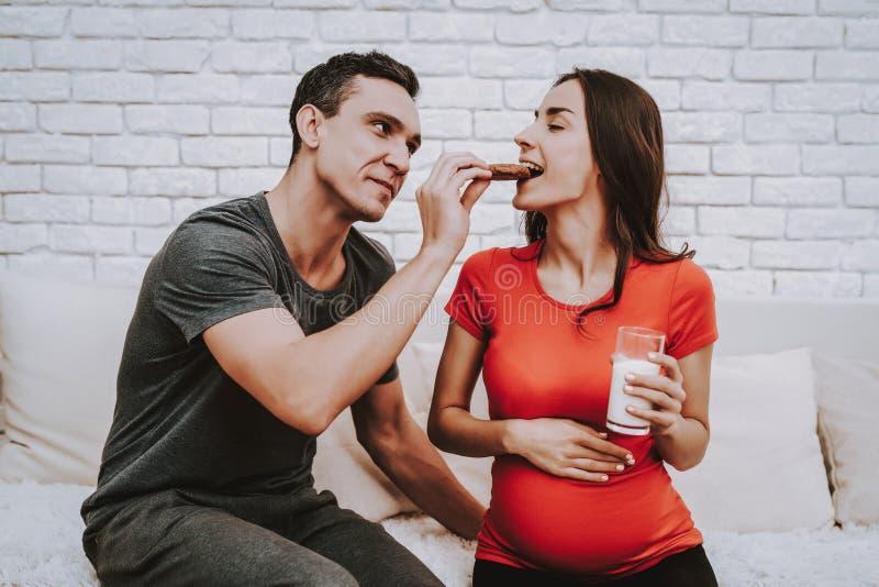 Una donna incinta ed il suo marito mangiano insieme i biscotti fotografia stock
