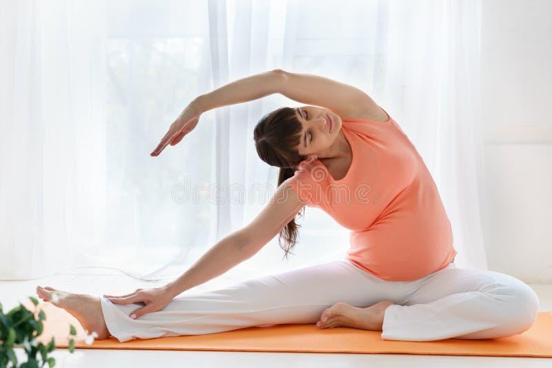 Una donna incinta europea con la maglietta rosa fa gli esercizi di yoga per carehealth suo ed il feto in camera da letto leggera  immagini stock