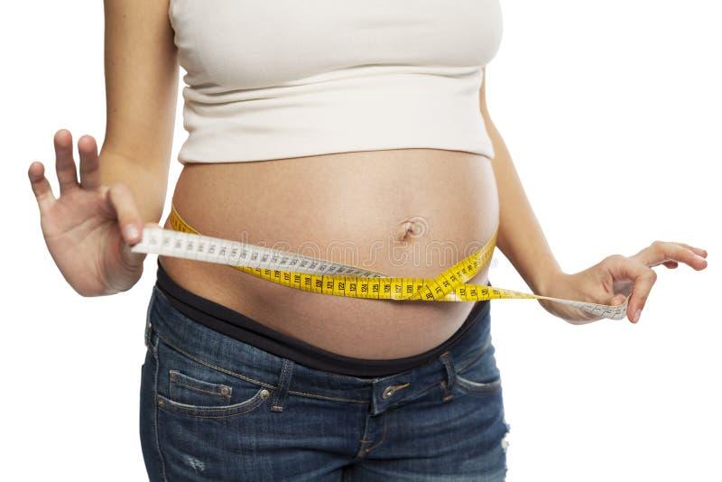 Una donna incinta misura la circonferenza addominale Isolato su una priorit? bassa bianca immagini stock libere da diritti