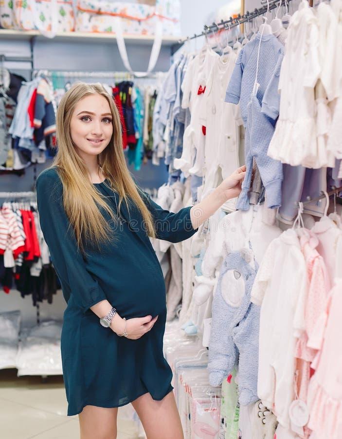 Una donna incinta sceglie i vestiti dei bambini nel deposito fotografia stock libera da diritti