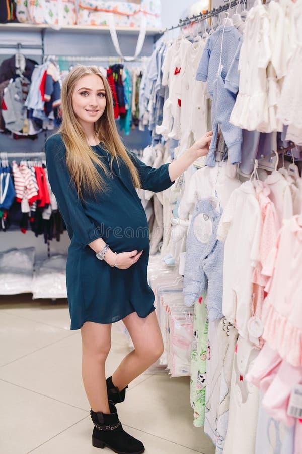 Una donna incinta sceglie i vestiti dei bambini nel deposito immagine stock