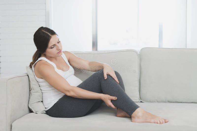 Una donna incinta si siede a casa su un sofà leggero La sua ferita delle gambe immagine stock