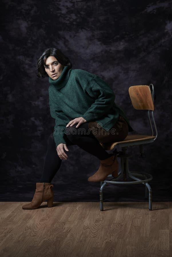 Una donna latina in attrezzatura di Autunno-inverno che si siede davanti ad un blac fotografia stock
