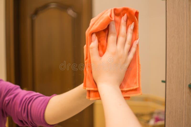 Una donna lava uno specchio con uno straccio speciale fotografie stock