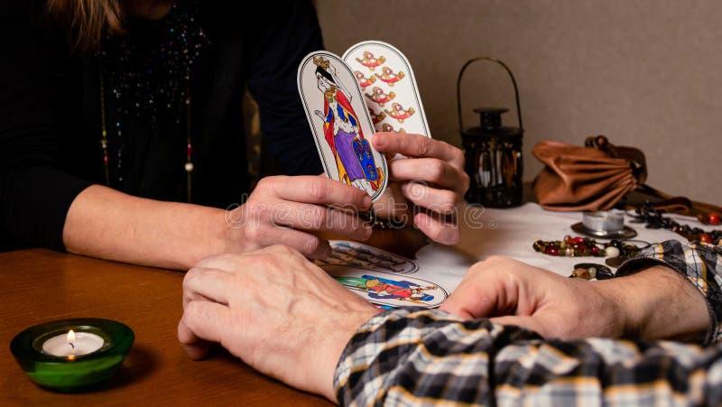 Una donna matura divina gli uomini sulle carte Il indovino contiene due carte e le mostra al cliente fotografia stock