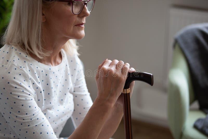 Una donna matura, strappata, in bicchieri con un bastone, sola fotografie stock