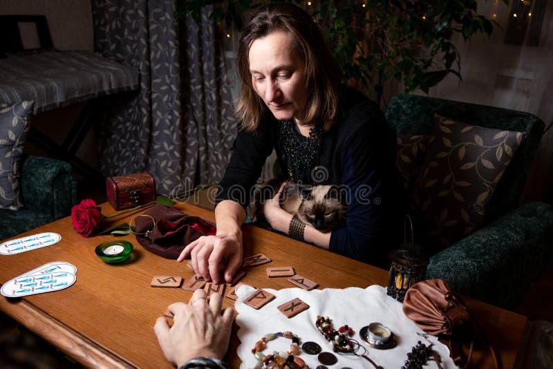 Una donna matura strega un cliente per l'uomo su piste di legno fotografia stock