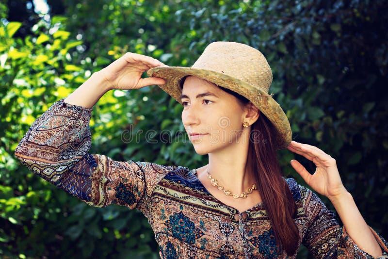 Una donna modesta e bella in un cappello di paglia fotografia stock