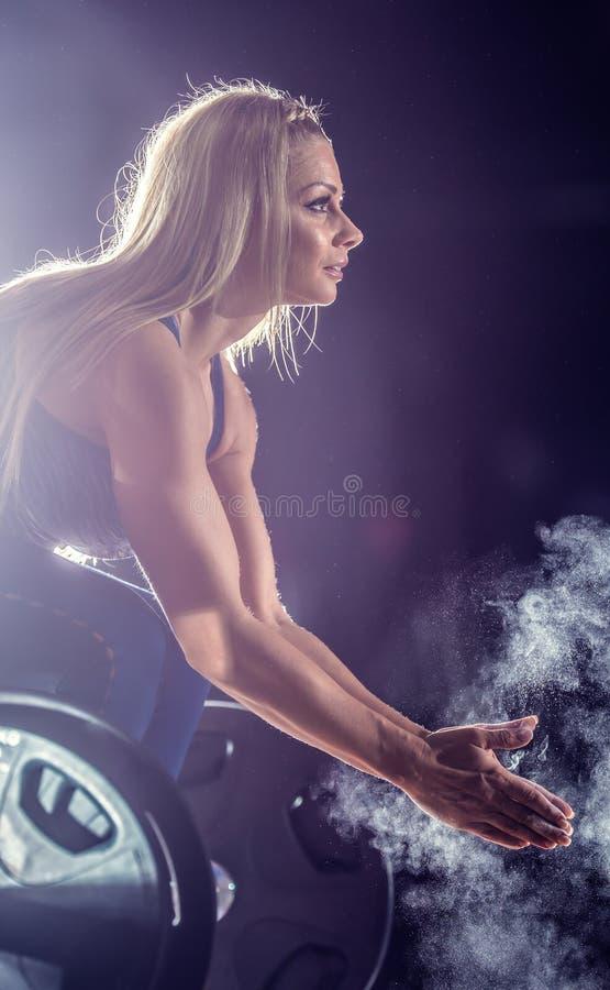 Una donna moscolare sollevatrice di pesi che applaude la mano prima che barbell si alleni in palestra con dei manganelli immagine stock libera da diritti