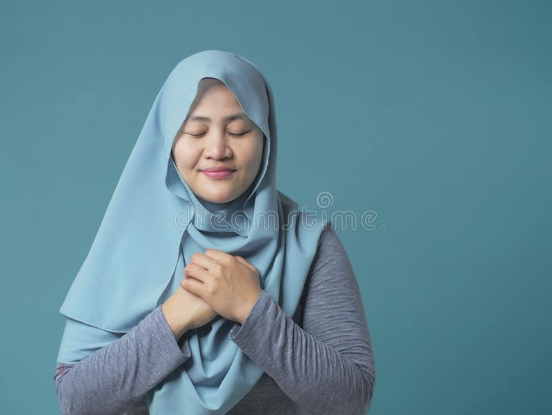 Una donna musulmana chiude gli occhi, mani sul cuore e preghiera immagine stock libera da diritti