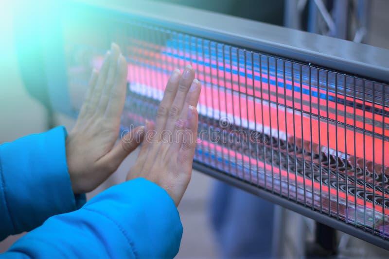 Una donna nei warmes di una giacca blu le sue palme immagine stock