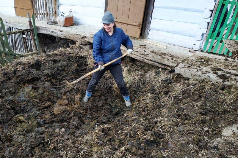 Una donna nella campagna sceglie il concime a partire dalla molla in anticipo del pozzo alla città fotografie stock