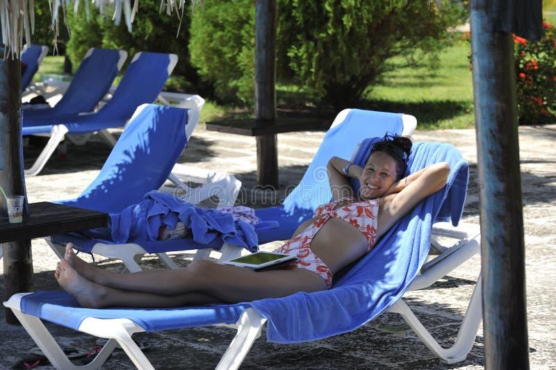 Una donna nella località di soggiorno di stazione termale in vestito di nuoto che prende i bagni del sole fotografia stock