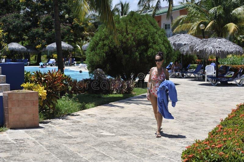 Una donna nella località di soggiorno di stazione termale in vestito di nuoto che prende i bagni del sole immagine stock
