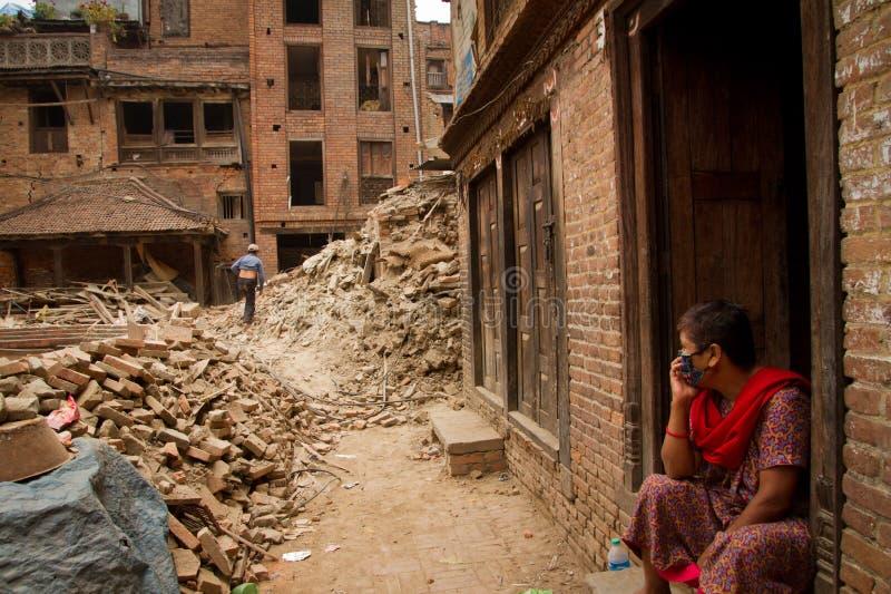 Una donna ora si siede fuori della sua casa rovinata terremoto in Bhaktapu immagine stock libera da diritti