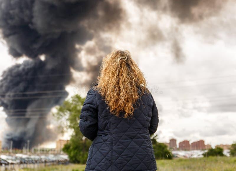 Una donna osserva un grande fumo venire da un fuoco immagine stock