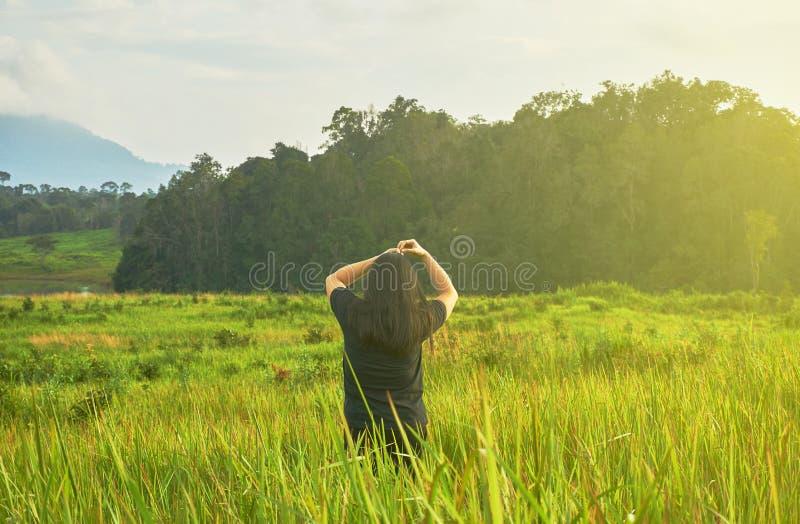 Una donna in panno nero sta stando nel campo di erba fotografia stock libera da diritti