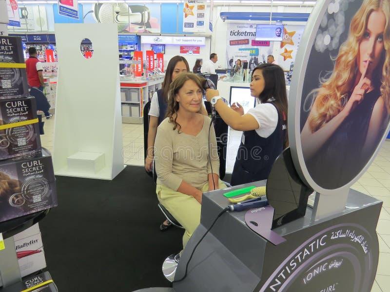 Una donna partecipa ad una campagna pubblicitaria Il venditore della ragazza fa i suoi riccioli con lo styler dei capelli nel cen fotografie stock