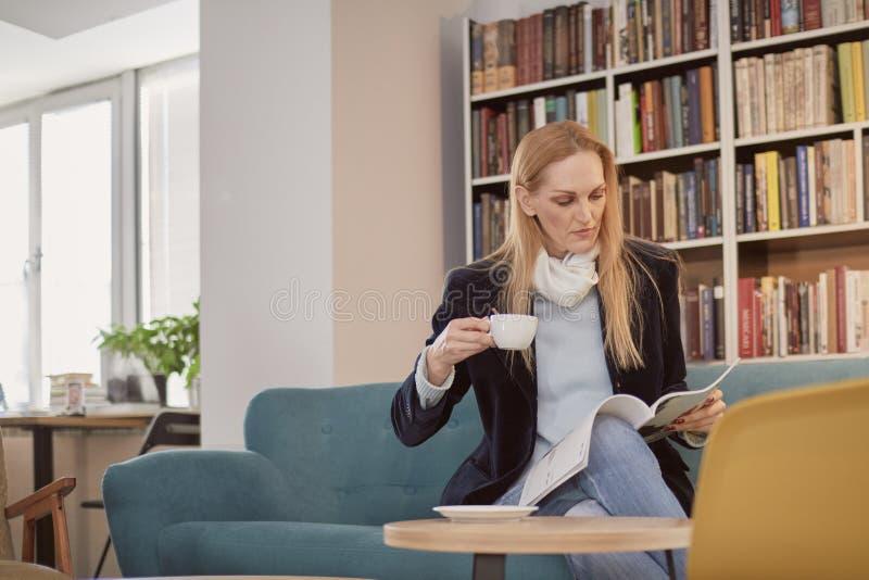 una donna, una persona 40 anni, tenendo la tazza di caffè, leggente rivista, in biblioteca, deposito di libro, negozio di libro,  fotografia stock libera da diritti