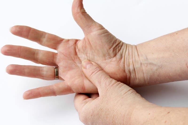 Una donna più anziana ha dolore in sue mani fotografia stock