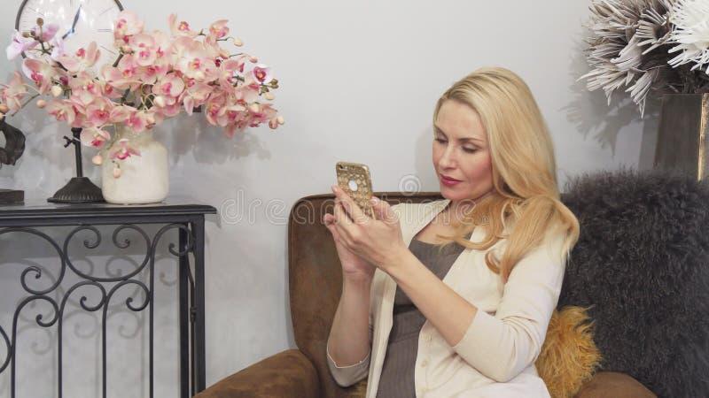 Una donna piacevole sta facendo il selfie sul suo telefono fotografia stock