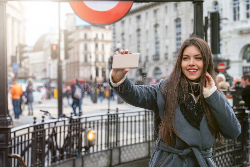 Una donna scatta foto di selfie al Piccadilly Circus nel centro di Londra, Regno Unito immagini stock