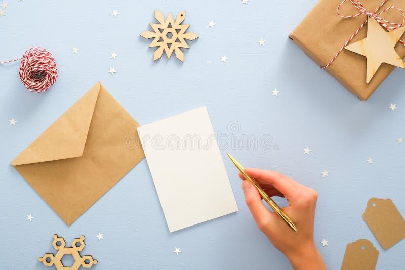Una donna scrive cartolina di invito natalizia su sfondo blu con decorazioni natalizie festose, coriandoli, stelle, fotografie stock libere da diritti