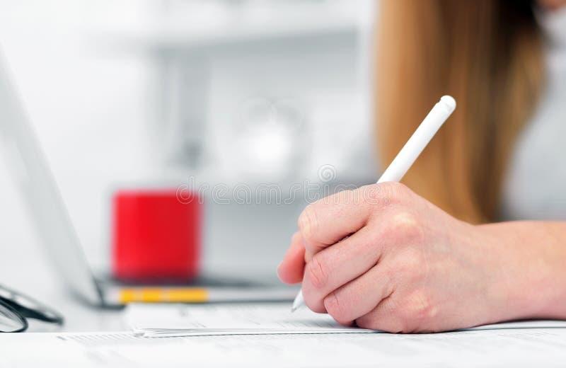 Una donna scrive mentre si siede ad una tavola in un ufficio o in un'aula La ragazza compila i documenti nel luogo di lavoro face fotografie stock libere da diritti