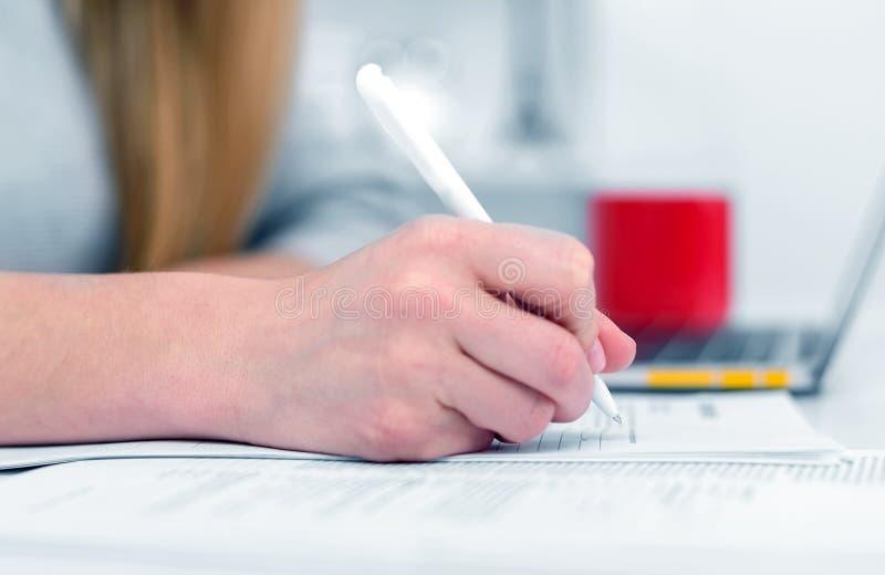 Una donna scrive mentre si siede ad una tavola in un ufficio o in un'aula La ragazza compila i documenti nel luogo di lavoro face immagini stock libere da diritti
