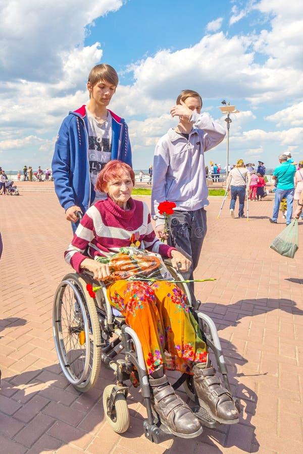 Una donna in una sedia a rotelle che tiene i garofani fotografie stock libere da diritti