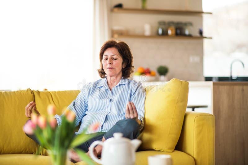 Una donna senior che si siede sul sofà all'interno a casa, facendo esercizio di yoga immagini stock