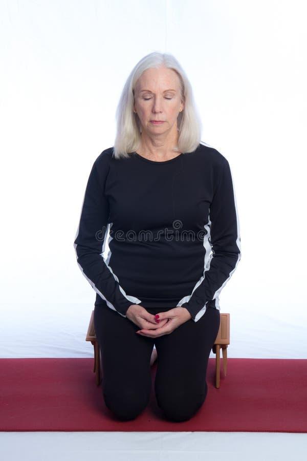 Una donna senior medita fotografia stock