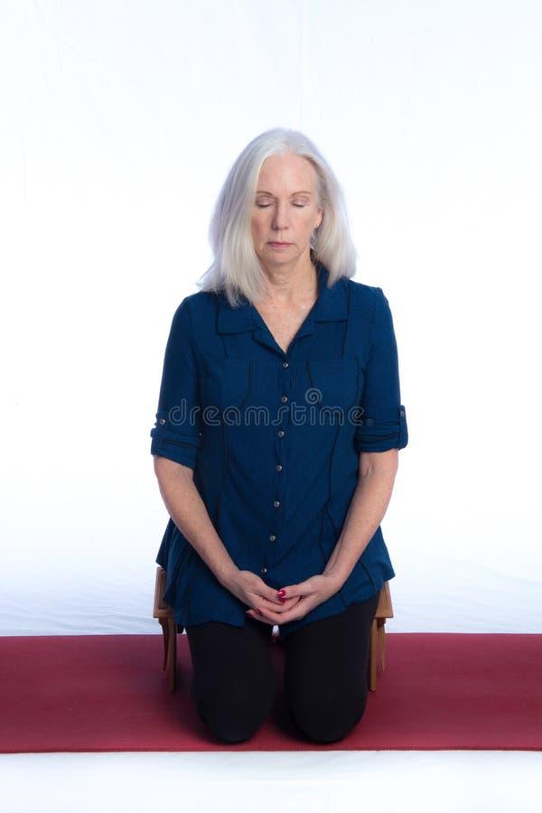 Una donna senior medita fotografia stock libera da diritti