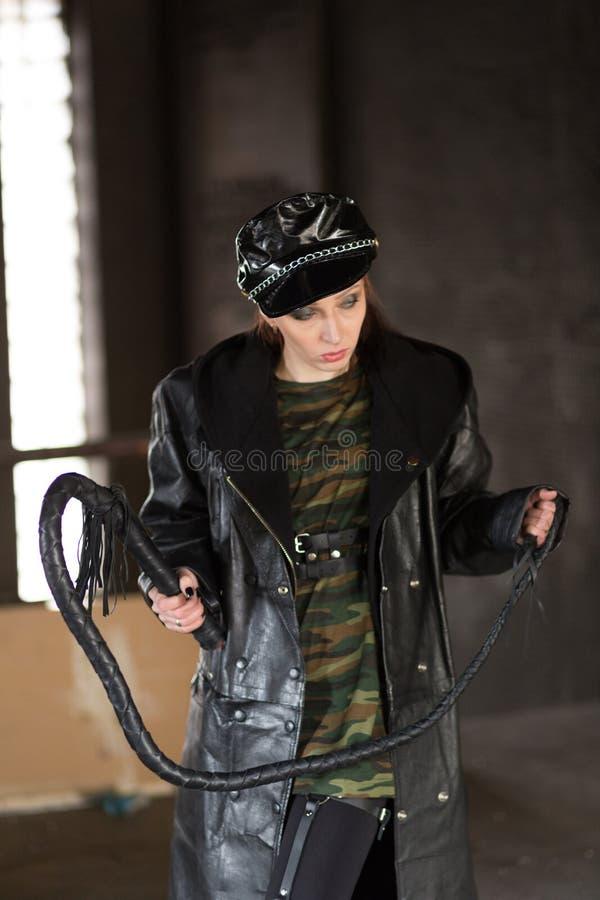 Una donna sensuale in un mantello nero con una frusta di cuoio La signora con la frusta Una ragazza con una frusta di cuoio come  fotografia stock