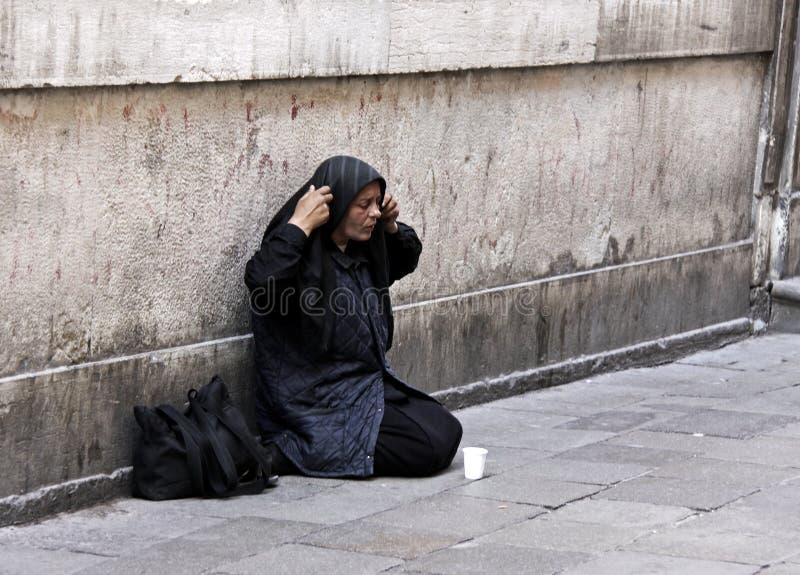 Una donna senza casa che elemosina a Venezia, Italia immagine stock
