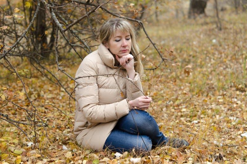 Una donna si addolora quaranta anni nella foresta di autunno fotografia stock